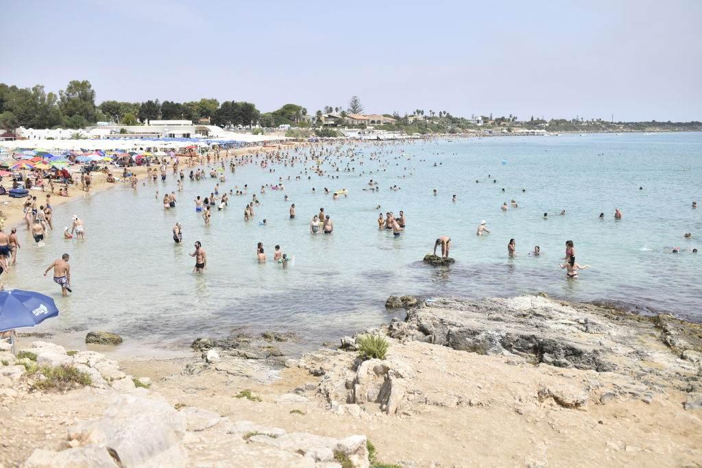Banhistas frequentam praia na ilha da Sicília, Itália, em dia quente/Getty Image