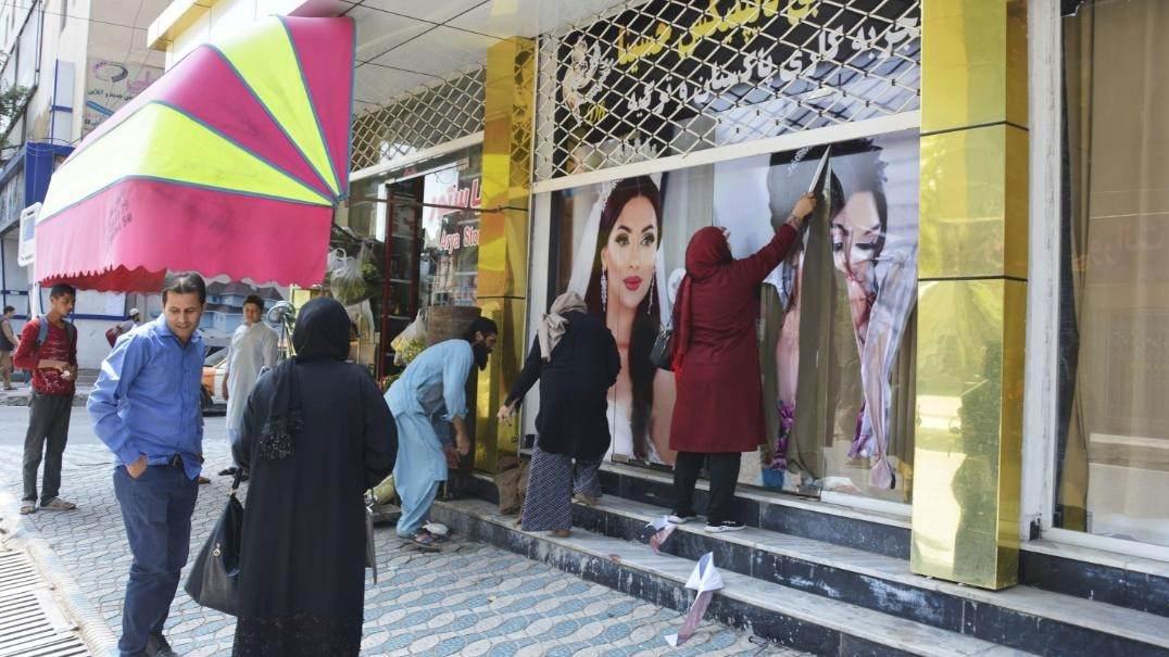 Trabalhadores cobrem fotos de mulheres em parede em Cabul