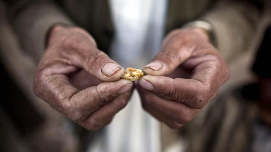 Homem afegão segura uma pequena peça de ouro, garimpada do local de uma mina proposta de Qara Zaghan em 2011