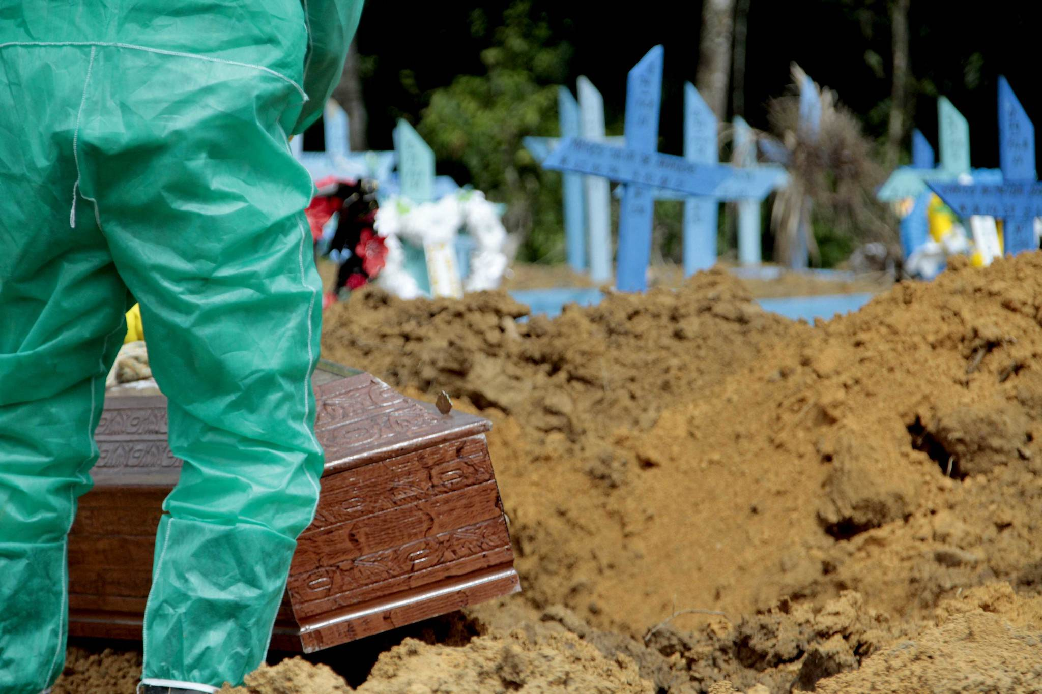 Coveiro em traje de proteção sepulta caixão em cemitério de Manaus