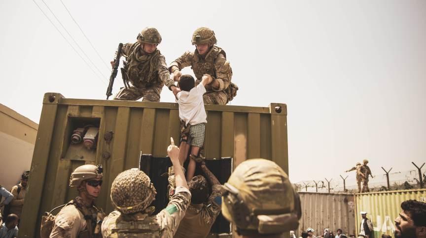 Soldados dos Estados Unidos puxando criança durante resgate em Cabul