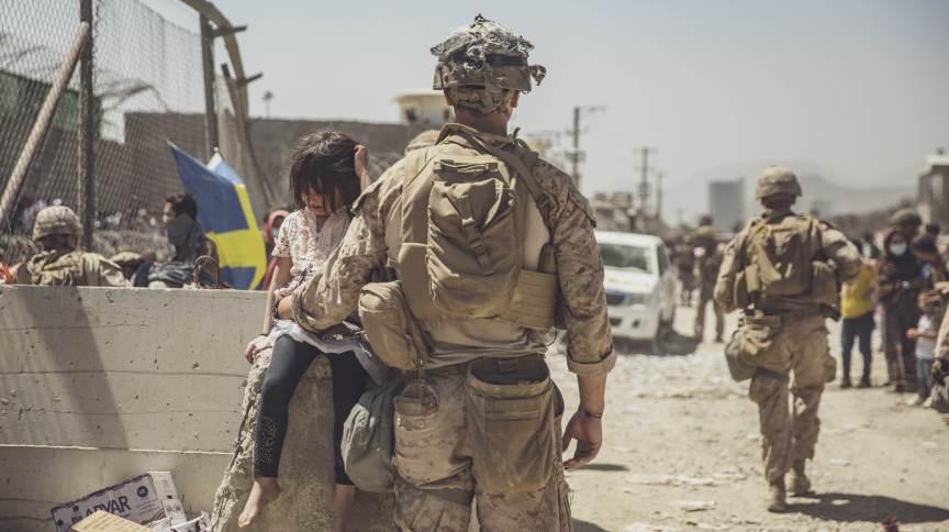 Soldado americano cuida de criança em um dos pontos de checagem no aeroporto de Cabul