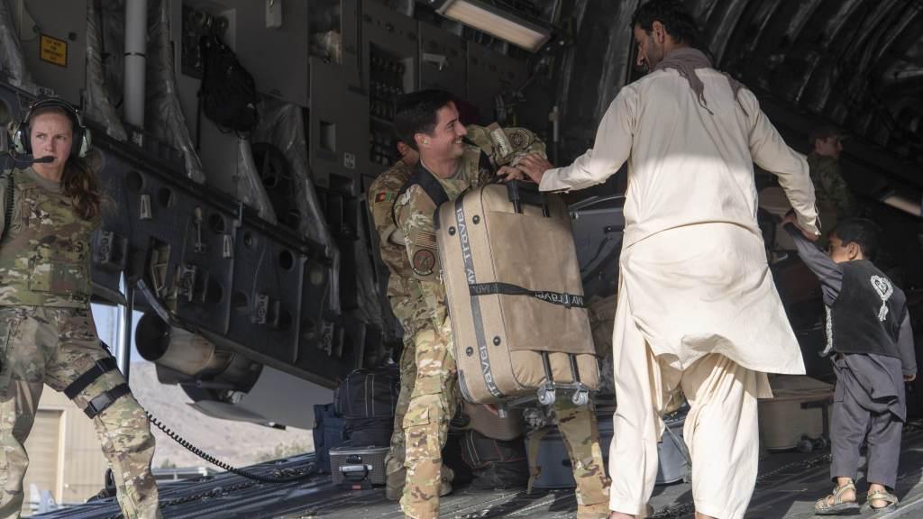 Soldado dos EUA ajuda afegão e seu filho a embarcarem em voo no aeroporto de Cabul