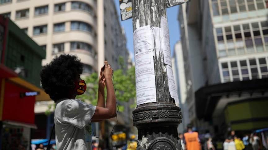 Mulher fotografa cartazes com oportunidades de emprego no centro de São Paulo 30/09/2020