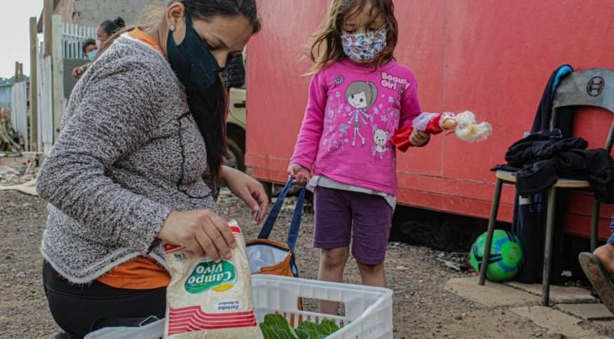 Família recebe alimentos em distribuição de cestas básicas em Curitiba (PR)