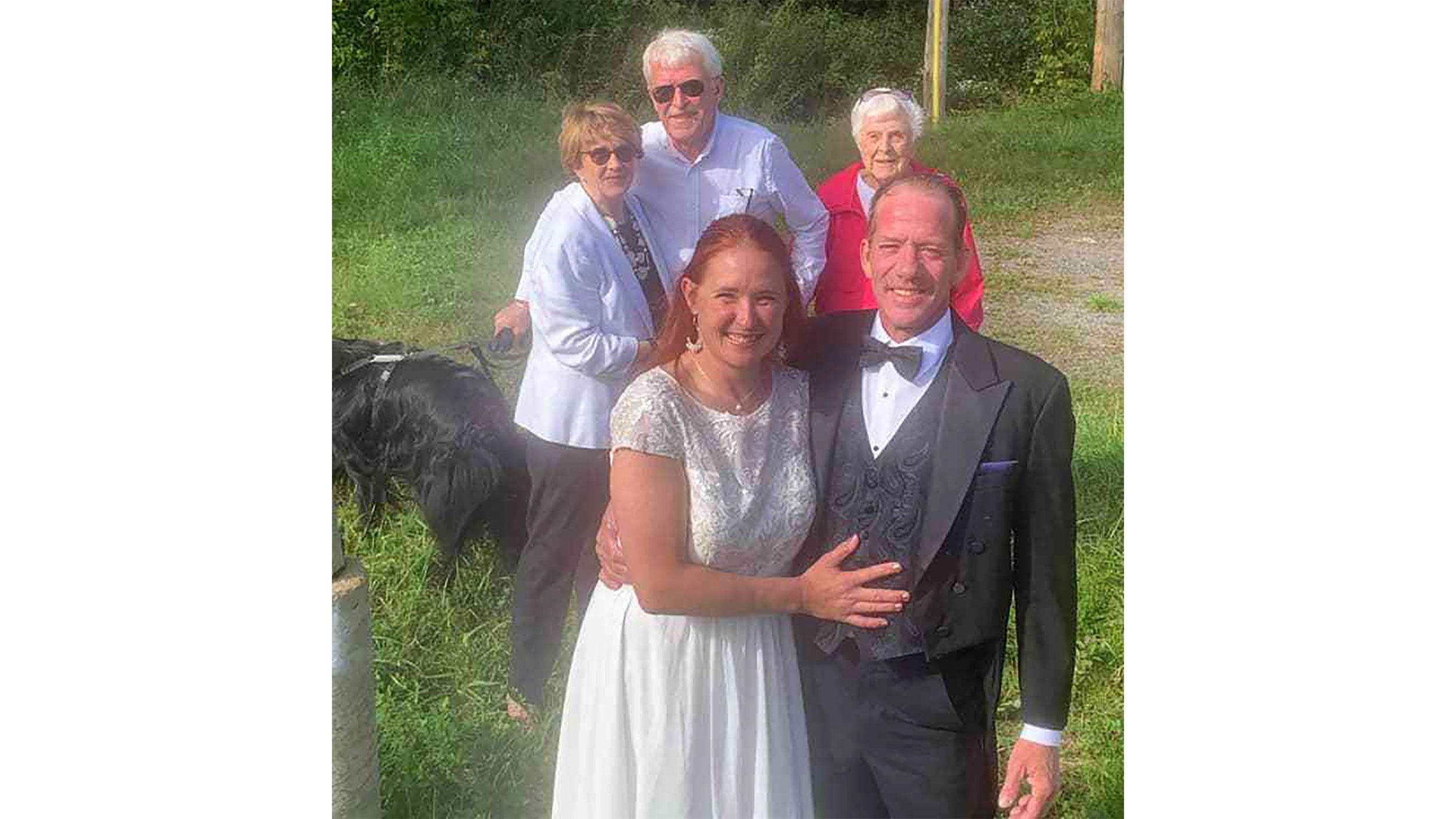 Brian Ray e Karen Mahoney, do lado norte-americano da fronteira, tiram foto com a família dela ao fundo, no lado canadense