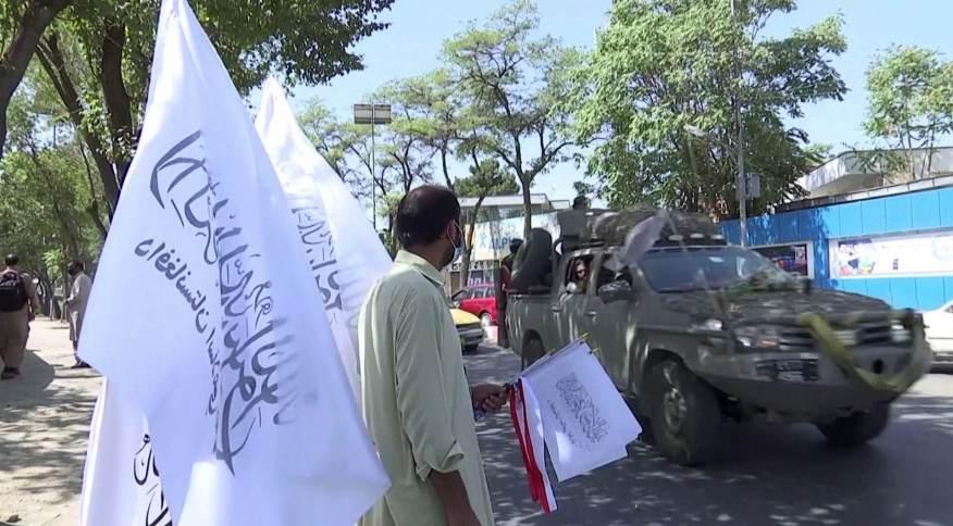 Homem vende bandeiras do Talibã em Cabul, Afeganistão