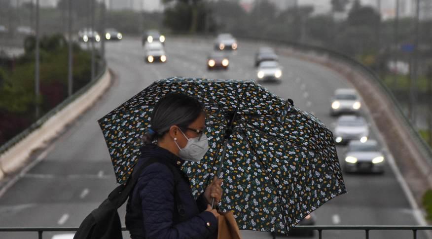 Pedestres se protegem do frio e da leve garoa, nesta manhã de quarta-feira (22), na Ponte do Jaguaré, em São Paulo (SP). Depois de um dia com temperatura máxima de 33ºC, a previsão é que hoje a máxima chegue a apenas 18ºC