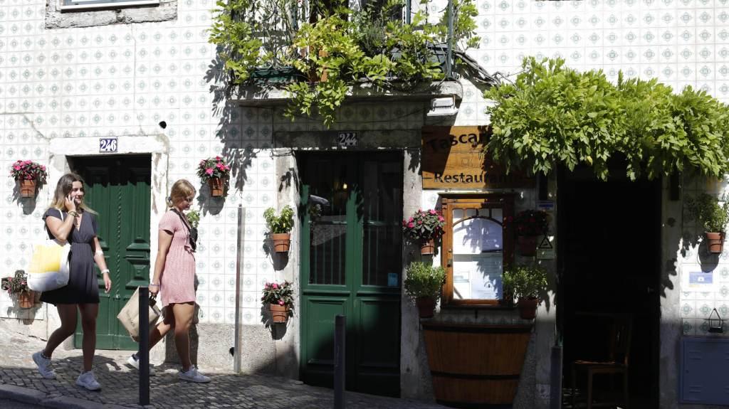 Mulheres passam por restaurante em Lisboa; Portugal reabre fronteiras para turistas brasileiros