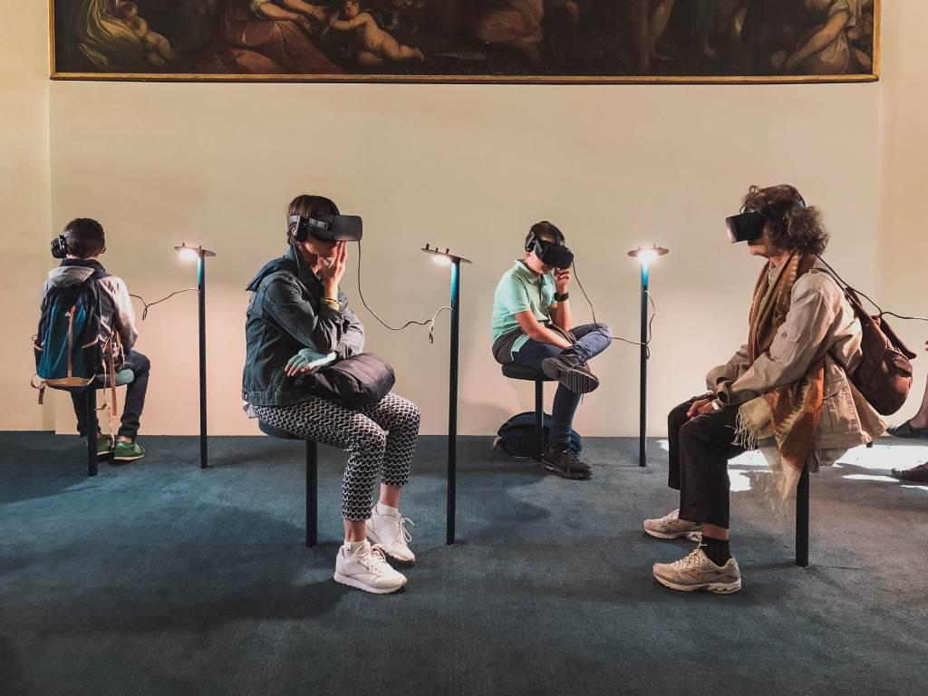 Quatro pessoas sentadas usando óculos de realidade virtual