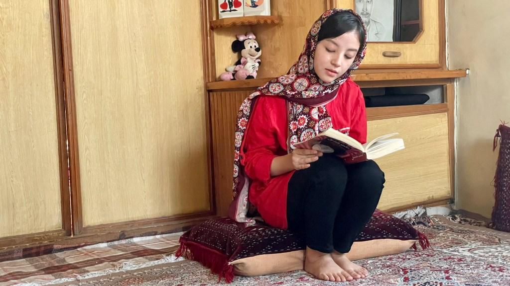 Estudante lê livro em casa