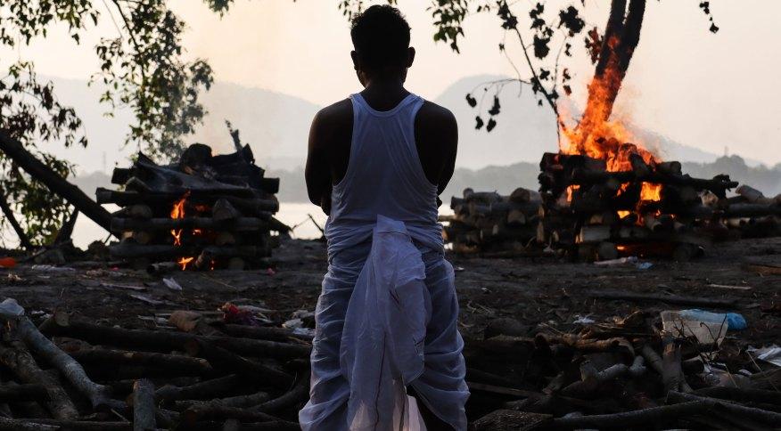 Familiar acompanha cremação de vítima da Covid-19 nas margens do rio Brahmaputra, em Guwahati
