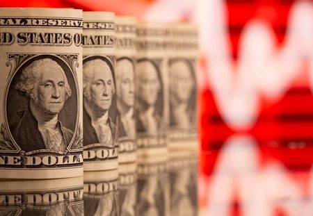 Notas de 1 dólar dos EUA retratadas em frente a um gráfico de preços de ações