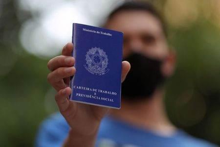 Homem mostra carteira de trabalho enquanto procura por vagas de emprego no centro de São Paulo