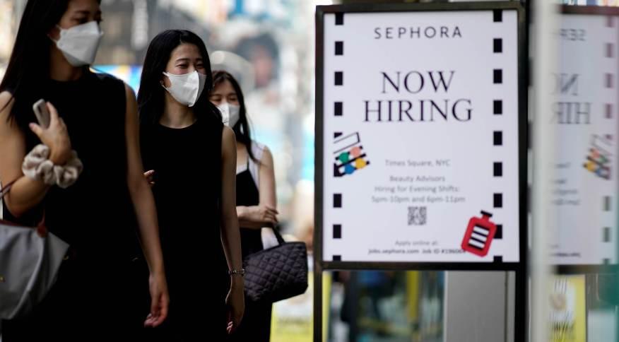Placa anunciando vagas de emprego é vista enquanto as pessoas entram em loja na cidade de Nova York