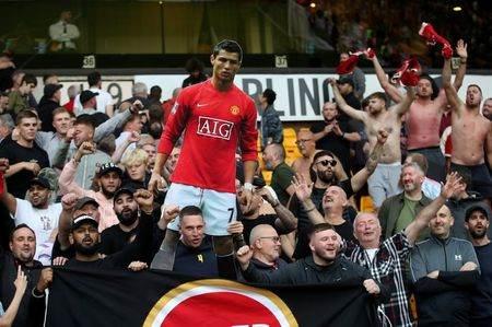 Torcedores do United com cartaz de Cristiano Ronaldo