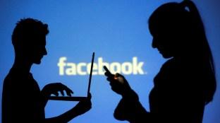 Silhuetas das pessoas posam com laptops em frente a uma tela projetada com o logotipo do Facebook, nesta ilustração fotográfica