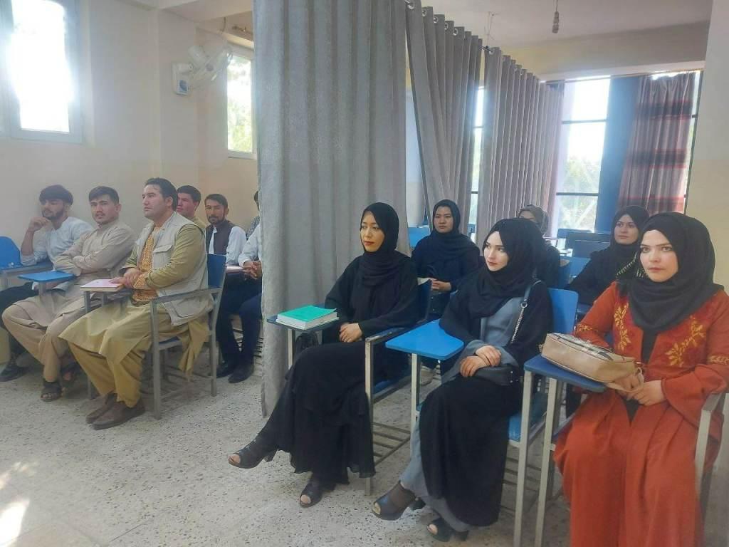 Sala de aula dividida por cortina em universidade de Cabul