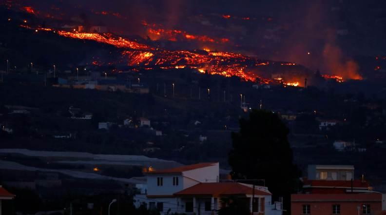 Lava por trás de casas após erupção de vulcão na ilha de La Palma, na Espanha